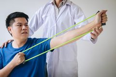 Doctor physiotherapist assisting a male patient while giving exercising treatment on stretching his arm with exercise band in the. Clinic, Rehabilitation royalty free stock image