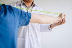 Doctor physiotherapist assisting a male patient while giving exercising treatment on stretching his arm with exercise band in the. Clinic, Rehabilitation royalty free stock photo