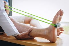 Doctor physiotherapist assisting a male patient while giving exercising treatment on stretching his leg on bed in the clinic.  stock photos