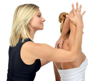 Doctor physiotherapist stretching a young sport woman isolated Stock Photography