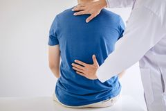 Doctor physiotherapist treating lower back pain patient after while giving exercising treatment on stretching in the clinic,. Rehabilitation physiotherapy stock image