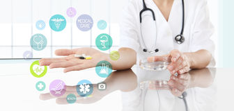 Doctor with pills in hand and colored icons. Health care concept. Doctor with pills in hand and colored icons. Health care and medical concept Royalty Free Stock Photography