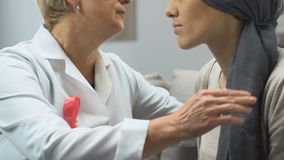 Doctor with pink ribbon comforting breast cancer patient, psychological support. Stock footage stock footage