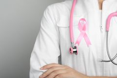 Doctor with pink ribbon and stethoscope on grey background. Breast cancer awareness. Doctor with pink ribbon and stethoscope on grey background, space for text royalty free stock image
