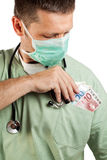 Doctor placing money in his pocket. Royalty Free Stock Photos