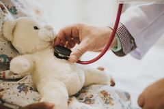 Doctor playfully checking the heart beat of a teddy bear stock images
