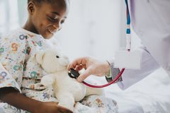 Doctor playfully checking the heart beat of a teddy bear stock photos