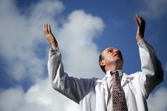 Doctor Playing God. Doctor with his arms raised to the blue sky wearing his white laboratory coat stock photography