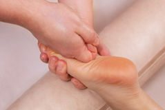 The doctor-podiatrist does an examination and massage of the patient`s foot stock photo
