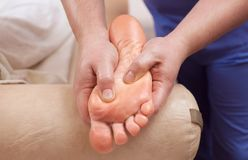 The doctor-podiatrist does an examination and massage of the patient`s foot. In the clinic Royalty Free Stock Photos