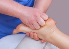 The doctor-podiatrist does an examination and massage of the patient`s foot. In the clinic Stock Photo
