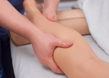Doctor-podiatrist does an examination and massage of the patient`s legs Stock Images