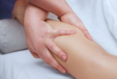 The doctor-podiatrist does an examination and massage of the patient`s legs stock image