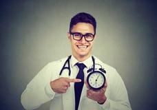 Doctor pointing at alarm clock stock photos