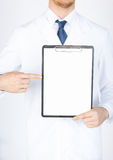 Doctor pointing at blank white paper Royalty Free Stock Images