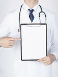 Doctor pointing at blank white paper Royalty Free Stock Photos