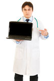Doctor pointing finger on laptops blank screen Stock Photo