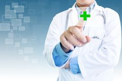 Doctor Pointing On Green Cross. Medical Care Concept Background Ideas Stock Photo