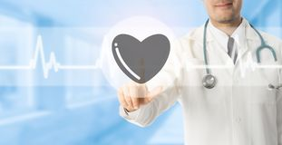 Doctor pointing at heart icon on blue background. Doctor pointing at heart symbol icon on blue hospital background. Medical and healthcare concept Stock Photos