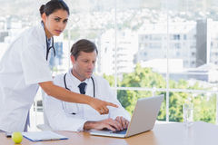 Doctor pointing at the laptop of a colleague Royalty Free Stock Images