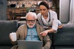 Doctor pointing at laptop in senior. Patient hands stock photo