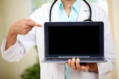 Doctor pointing in laptops blank screen Stock Photos