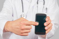 Doctor is pointing on mobile phone, copyspace Royalty Free Stock Photography