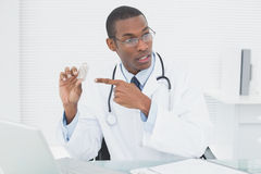 Doctor pointing at prescription bottle in medical office Royalty Free Stock Photo