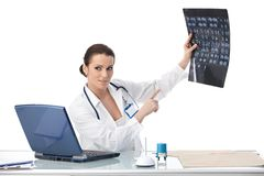 Doctor pointing at x-ray image. Explaining scan, sitting in office, smiling Stock Image