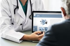 Doctor Pointing at Tablet Laptop royalty free stock images
