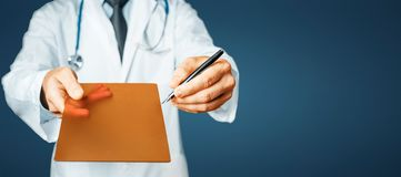 Doctor Pointing Your Prescription On A Digital Tablet Screen On Blue Background. Doctor in white coat with stethoscope holds in his hand  digital tablet with Royalty Free Stock Images