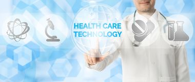 Doctor Points at HEALTH CARE TECHNOLOGY and Icons. Medical Research Concept - Doctor points at HEALTH CARE TECHNOLOGY with icons showing symbol of technology Royalty Free Stock Photos