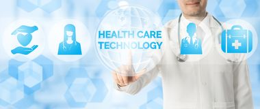 Doctor Points at HEALTH CARE TECHNOLOGY and Icons. Medical Research Concept - Doctor points at HEALTH CARE TECHNOLOGY with icons showing symbol of technology Stock Image