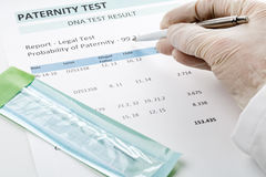 Doctor points at result on paternity test result form. Paternity DNA test result chart form - doctor pointing at result value stock photos
