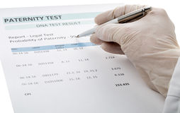 Doctor points at result on paternity test result form. Paternity DNA test result chart form - doctor pointing at result value royalty free stock image