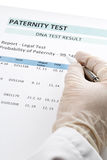 Doctor points at result on paternity test result form. Paternity DNA test result chart form - doctor pointing at result value royalty free stock images