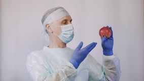 The doctor points to an apple. And the gesture makes it clear that these are the best natural vitamins for health. Close-up stock video footage