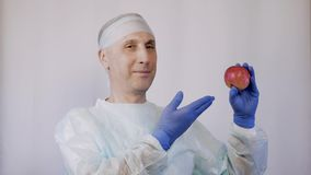 The doctor points to an apple. And the gesture makes it clear that these are the best natural vitamins for health. Close-up stock video