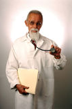 Doctor Portrait. A portrait of a middle-aged doctor on a white background. He is holding a stethoscope in one hand and a file folder in the other Royalty Free Stock Image