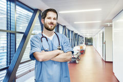 Doctor portrait modern clinic frontal OP. OP doctor portrait with stethoscope draped head on the corridor in hospital with beds royalty free stock photo