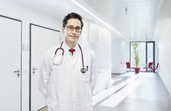Doctor portrait modern clinic frontal. Doctor portrait with stethoscopes draped head in the hallway in the hospital with table and red chairs stock photography