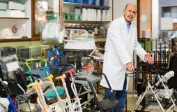 Doctor posing near orthopaedic equipment. Doctor posing near display with orthopaedic equipment and machines stock photos