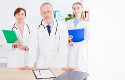 Doctor posing in office with medical staff, wearing a stethoscope royalty free stock photos