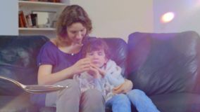 Doctor pouring cough syrup in a spoon on the background of a mother with a sick, feverish child.  stock video footage