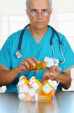 Doctor pouring pills into his hand royalty free stock photos