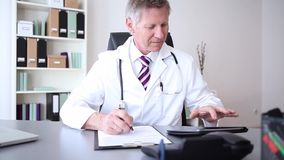 Doctor or practitioner with digital tablet while writing notes stock footage