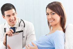 Doctor and pregnant patient. On bed at clinic Stock Photo