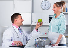 Doctor and pregnant visitor. Middle-aged pregnant visitor consulting smiling men doctor in hospital Royalty Free Stock Photography