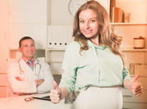 Doctor and pregnant visitor. Middle-aged pregnant visitor consulting smiling men doctor in hospital Royalty Free Stock Image