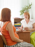 Doctor and pregnant woman. Mature doctor and pregnant women in clinic Stock Images